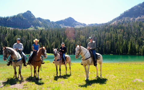 Four people atop horses in front of a lake in the mountains