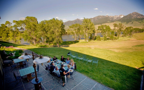 Outdoor dining patio overlooking a large field, lake and mountains
