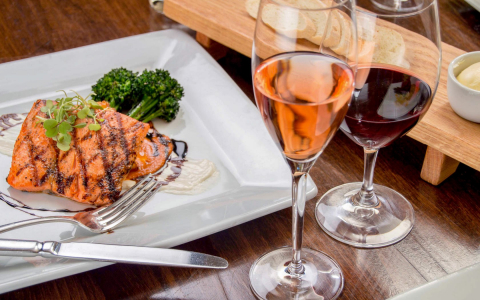 Plate of grilled salmon and broccoli with two glasses of wine