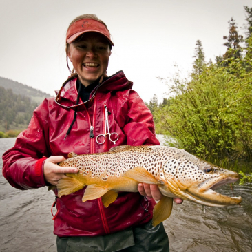 Woman standing in a river smiling while holding a large fish