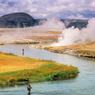 Two people standing in a winding river fishing with smoke and mountains in the background