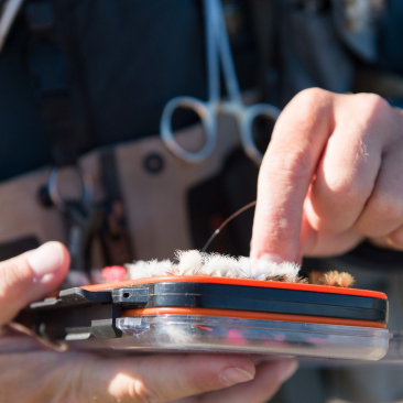 Close up shot of a man holding a case with fishing equipment