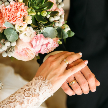 Close up of bride and grooms hands together with wedding rings and a pink, green and white bouquet of flowers