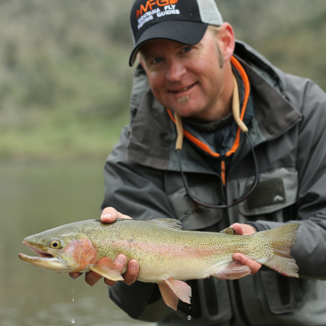 Man smiling while holding a green and pink fish