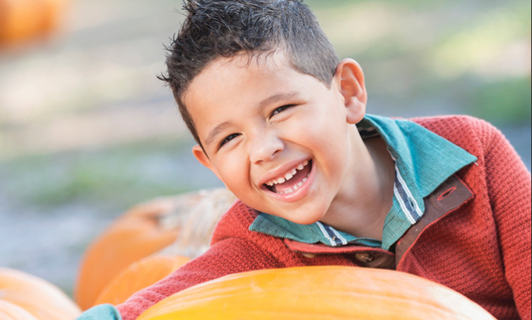 Cheerful kid next to pumpkins