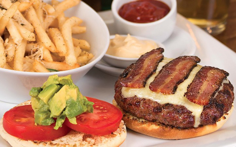 Hamburger topped with cheese and bacon served with tomatoes, avocado and french fries
