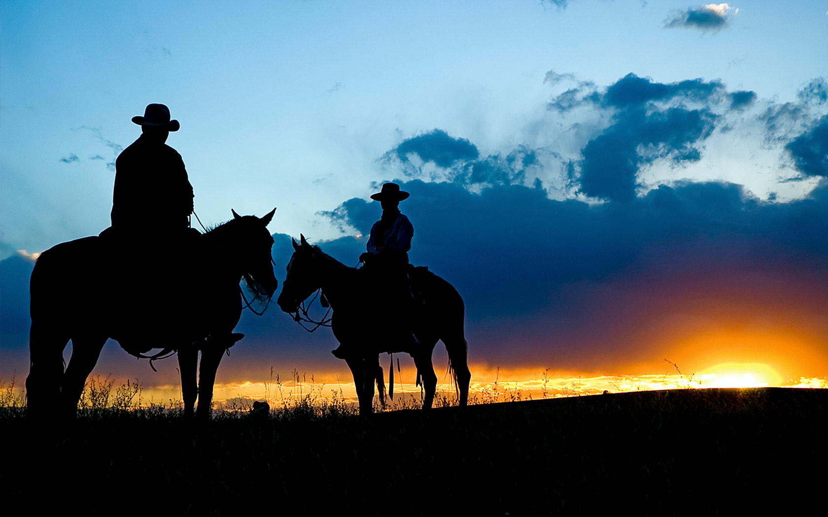 Silhouette of cowboys on horses at sunset