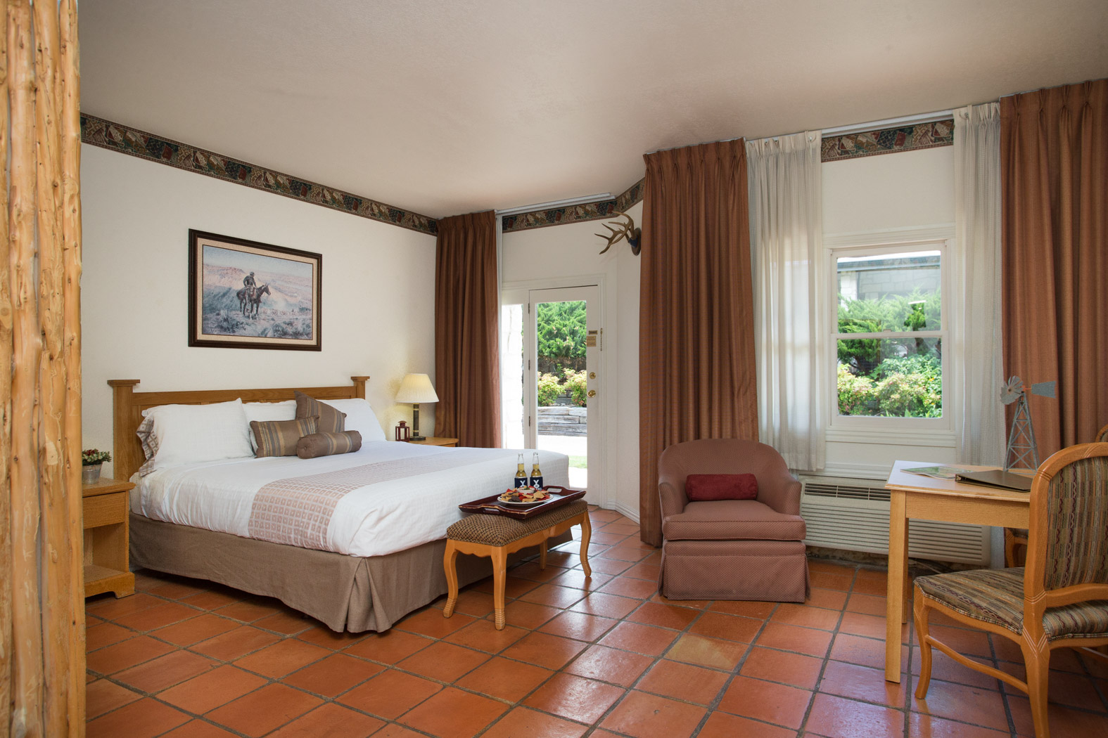 room with mexican tile floors, king bed, adjacent to double doors leading outside and seating area