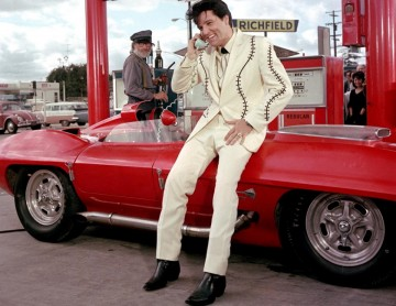 Elvis Presley leaning against red car