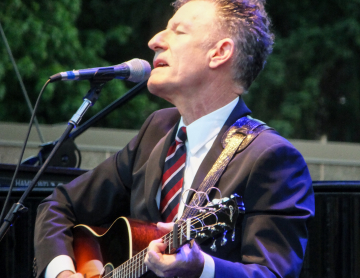 Lyle Lovett Playing Guitar at Outdoor Concert
