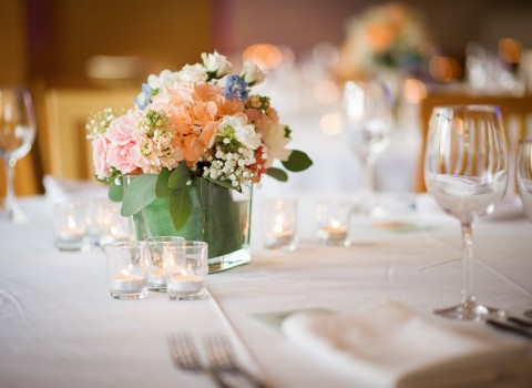 Table set up for a wedding ceremony with white linens, wine glasses, mini candles and a floral center piece