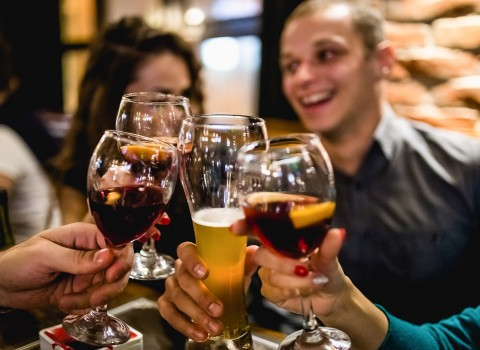 Group of friends clinking glasses with sangria and beer
