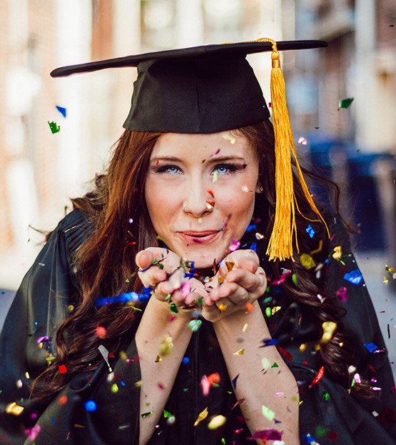 graduate blowing confetti