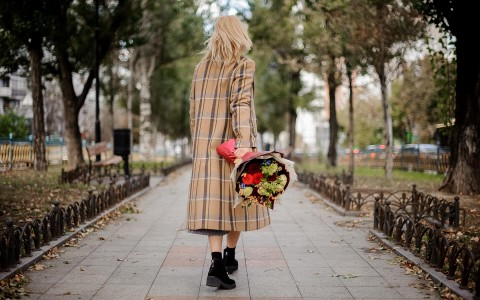 woman on sidewalk with bouquet of flowers