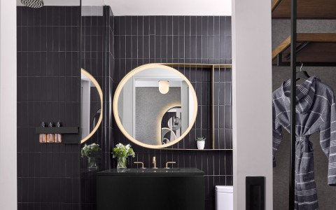 bathroom with black walls and gold mirror