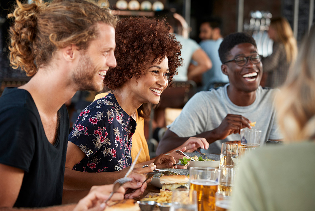 group of friends laughing around lunch table with food and drinks