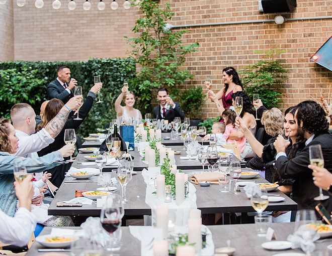 wedding party holding up champagne flutes and celebrating a wedding outdoors