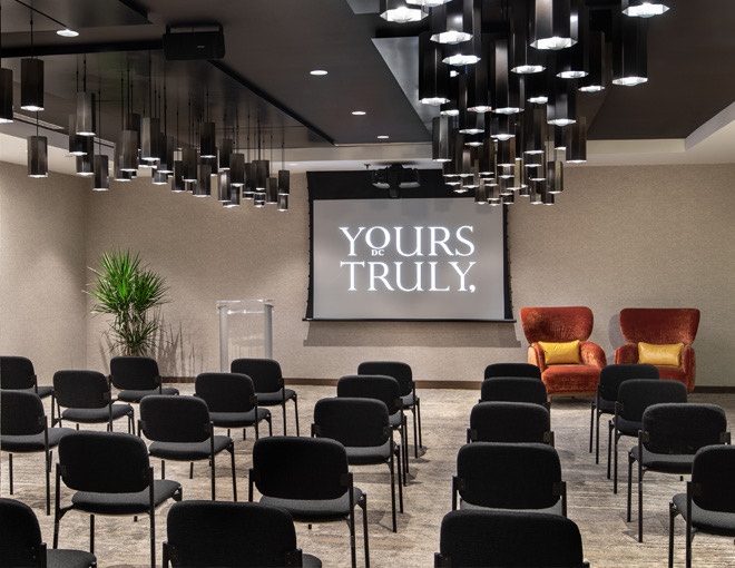 room with chairs lined up and a projector with the yours truly logo displayed