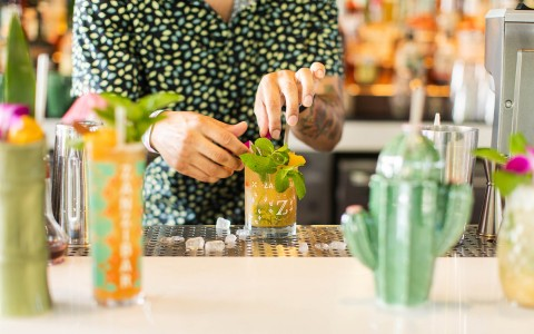 bartender topping cocktail with garnish