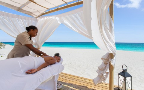 a woman getting a massage on the beach in a cabana