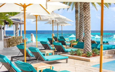 lounge chairs with umbrellas by the pool overlooking the ocean