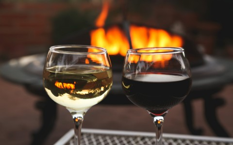 wine glasses in front of fire - gallery image
