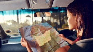 Woman in car reading a map