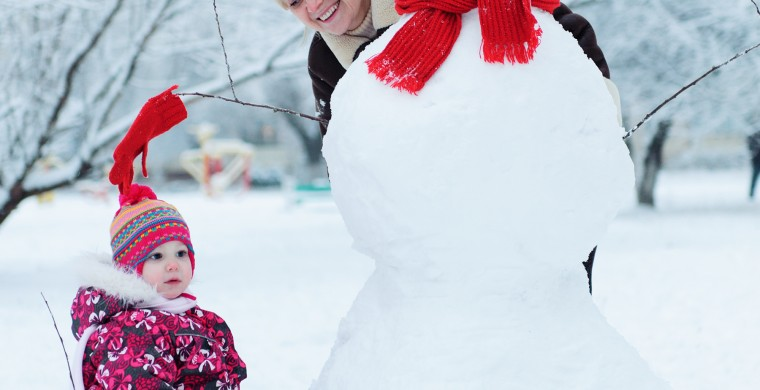 Mother and daughter wrapped up warm next to a giant snowman