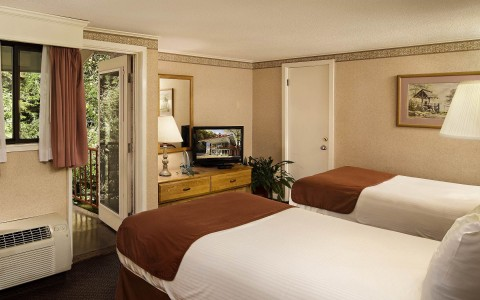 Room with two double beds, a TV, individual climate control unit and entrance to balcony