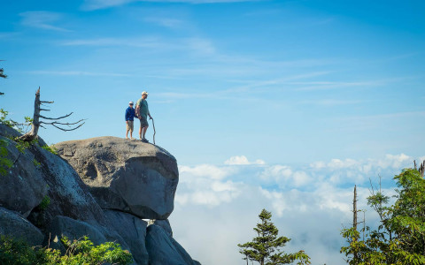 Hikers looking out over a mountaintop boulder