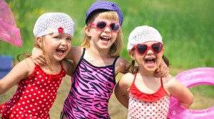 Three little smiling girls in bathing suits and hats