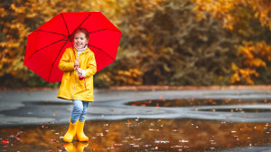 little girl in a yellow rain coat with yellow rain boots and a red umbrella splashing in puddles