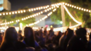 Festival goers under a string of lights on a lawn