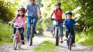 Family of four riding bikes down a country lane