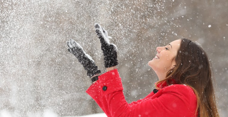 Young woman plays in the the snow