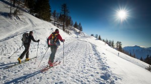 Skiers head along a snow path