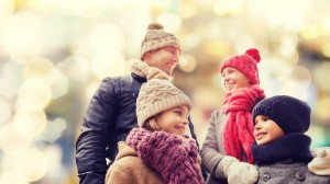 Smiling family of four wrapped up in hats, scarfs and gloves