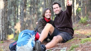 Young couple with backpack resting in a forest