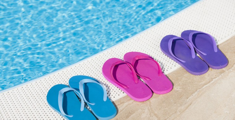 Three pairs of flip flops beside a pool