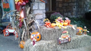 Fall decorations with decorated pumpkins, corn, hay bales and ribbons