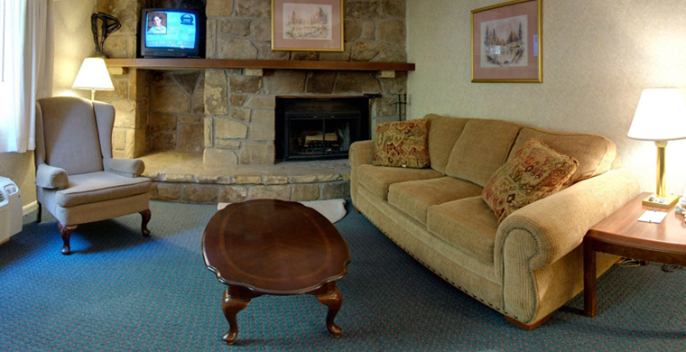 Executive Suite Seating area with sofa, wingback chair, coffee table, fireplace and TV